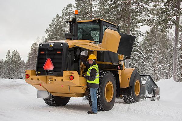 Construction Worker with Caterpillar Equipment in Winter