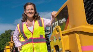 Women construction worker posing next to a piece of Caterpillar equipment